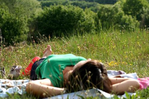 Kobieta śpiąca na polanie